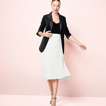 woman with hair in bun wears white skirt, black shirt and black tuxedo jacket