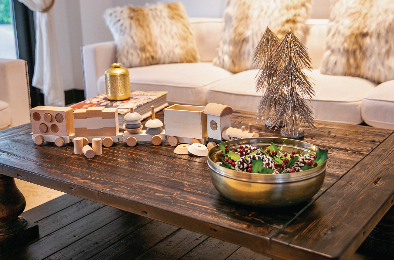 A wooden train is displayed on a coffee table with luxe gold accents