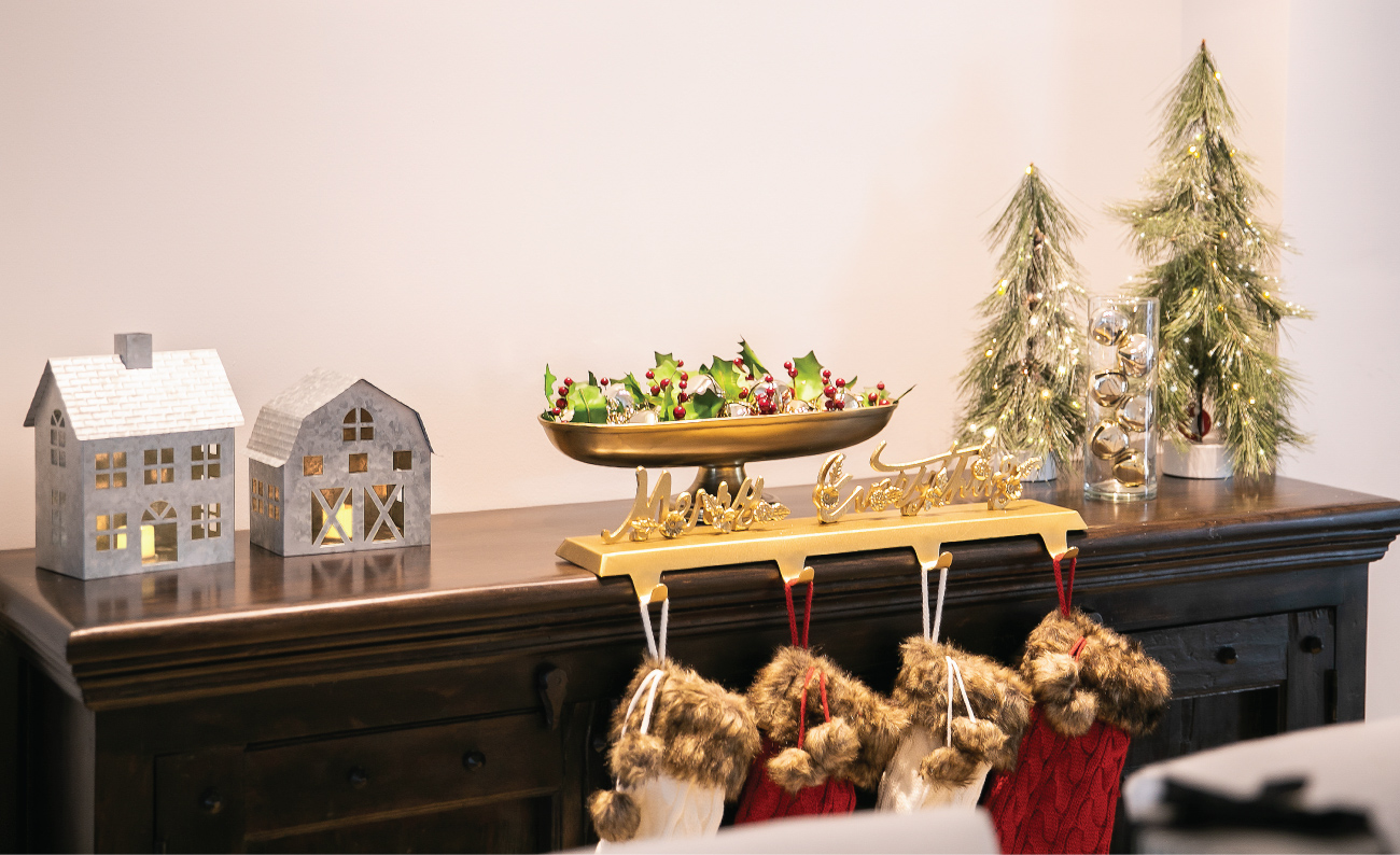 A table is decorated with a stocking holder, lighted trees and tin house and barn lanterns