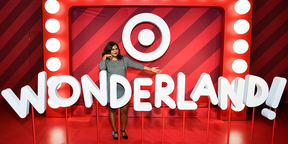 Mindy Kaling poses in front of a Wonderland! marquee