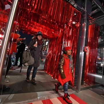 People walk through a tunnel of red tinsel