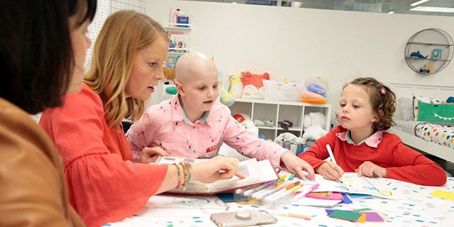 Two Target designers and two young girls sit at a table designing with art supplies