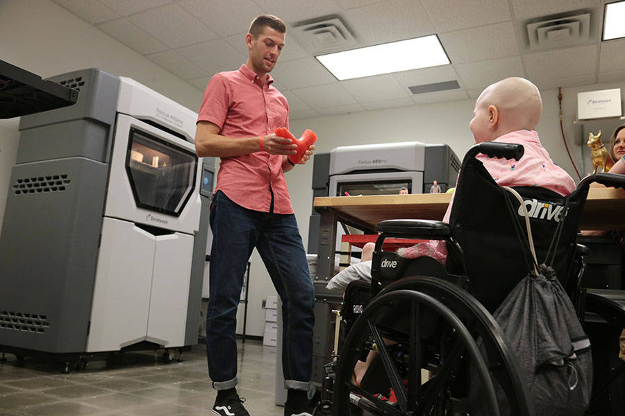 Hallie in her wheelchair looks on as an engineer does a demo in the 3D Design Lab. There are two 3D printers behind him.