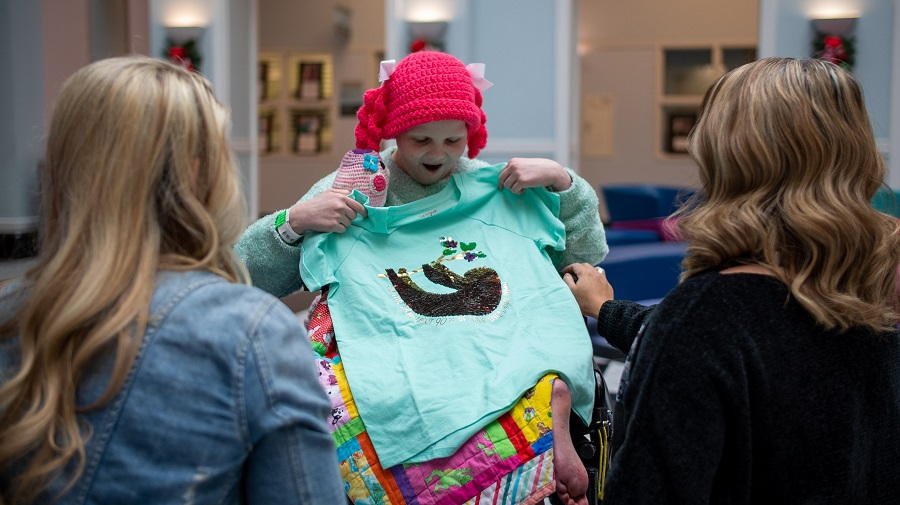Hallie, wearing a pink beanie, smiles as she holds up a mint green sloth tee she just unwrapped as two designers look on
