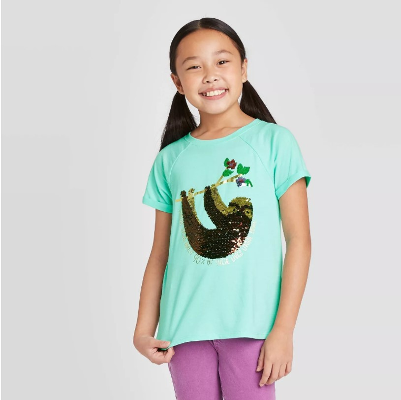 A young girl with pigtails models a mint green tee with a shiny brown and gold sequined sloth hanging from a tree branch.
