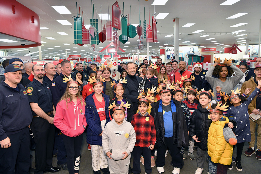 Donnie Wahlberg poses with a large group of officers, kids and team members. Many are in uniform and wearing paper reindeer antlers.
