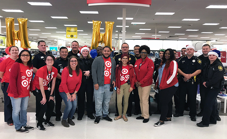 Team members in red shirts holding gold H balloons pose with their law enforcement partners in a Target aisle.