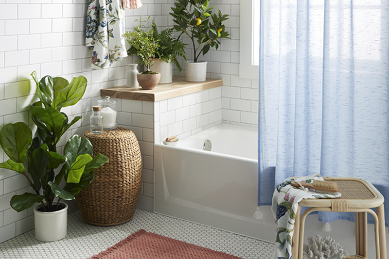 A bathroom brimming with faux greenery and airy blue curtain