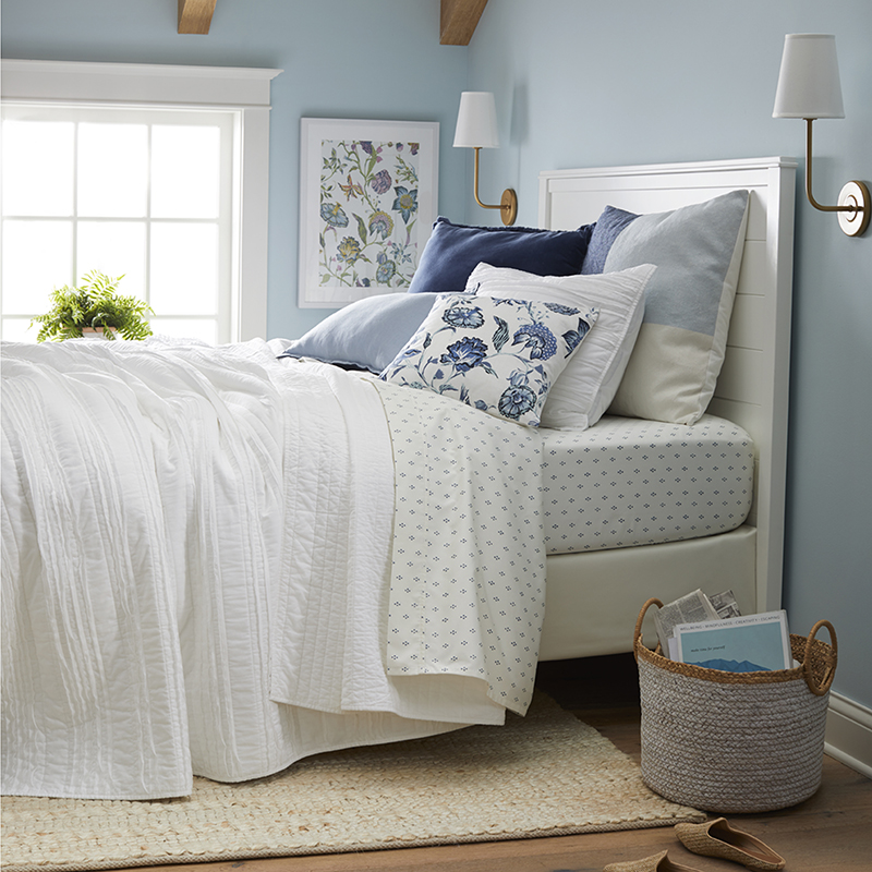 A bedroom bedecked in crisp whites and cool blues