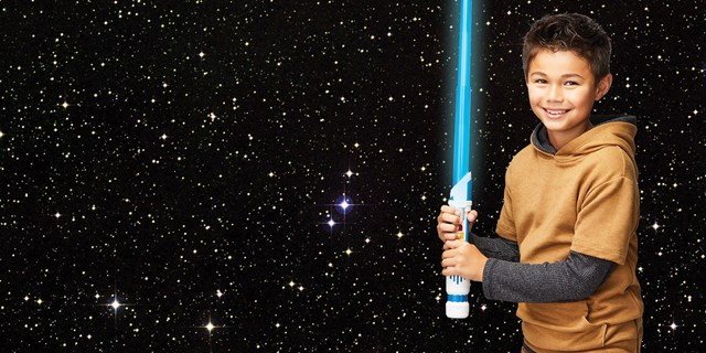 A young boy stands against a starry space background holding a blue toy lightsaber.