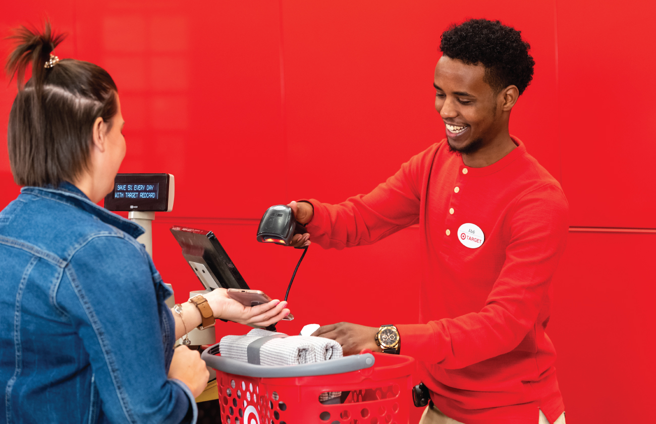 A team member in a red shirt scans a guest's smartphone at the checkout counter against a red wall.