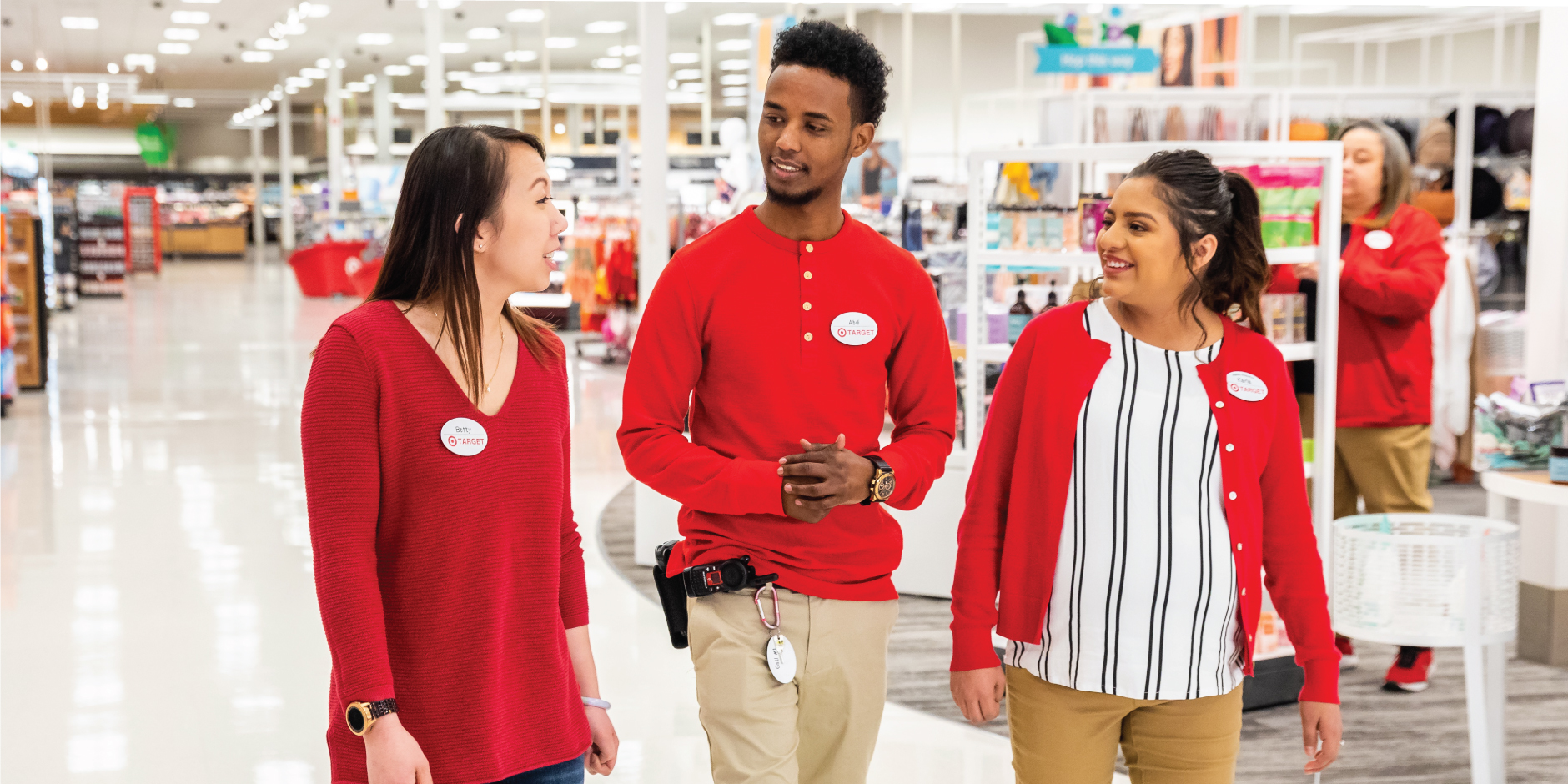 Three team members wearing red shirts talking as they walk a Target aisle