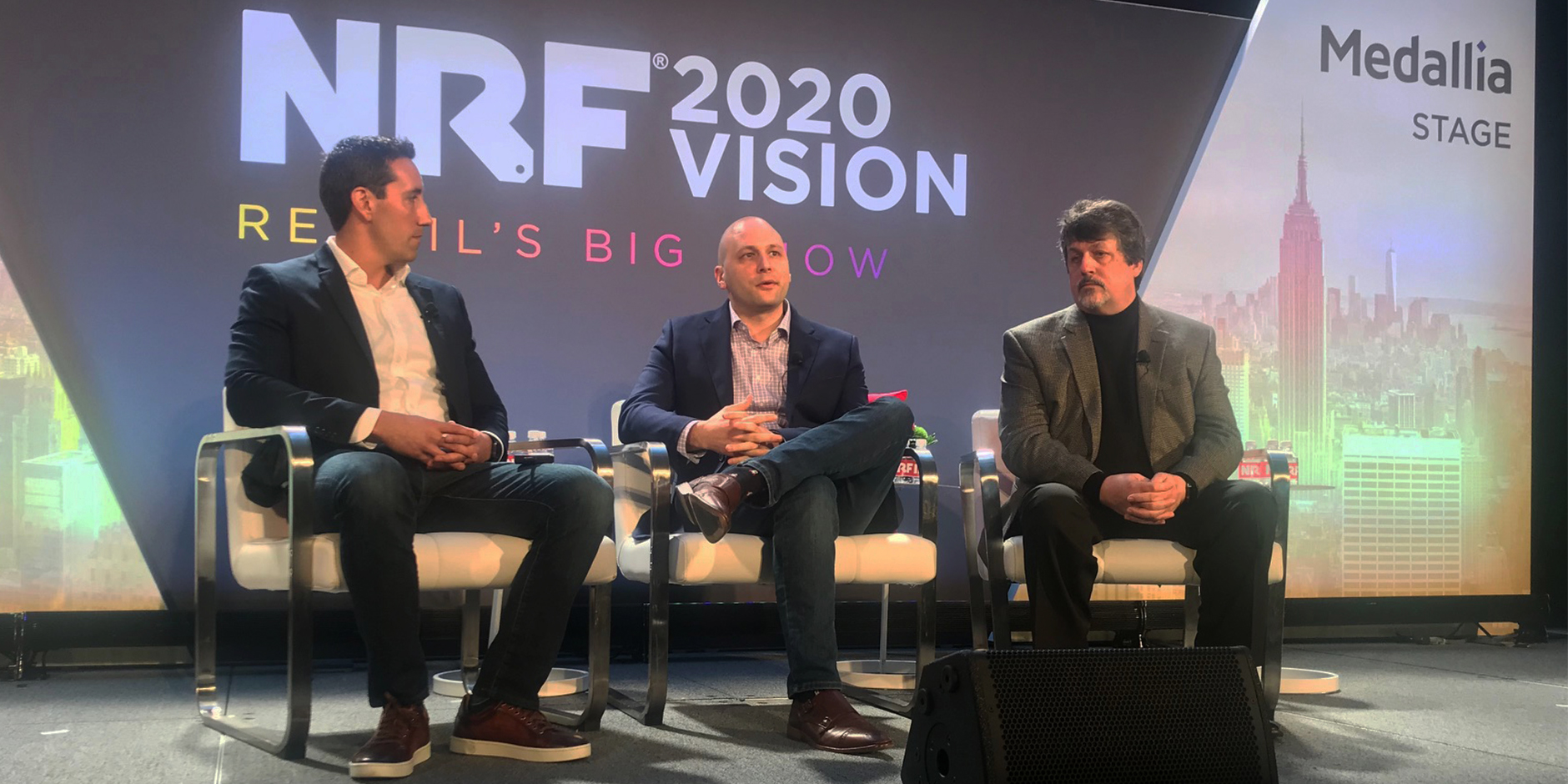 Three men sit in chairs onstage in front of a big screen showing the NRF Big Show logo
