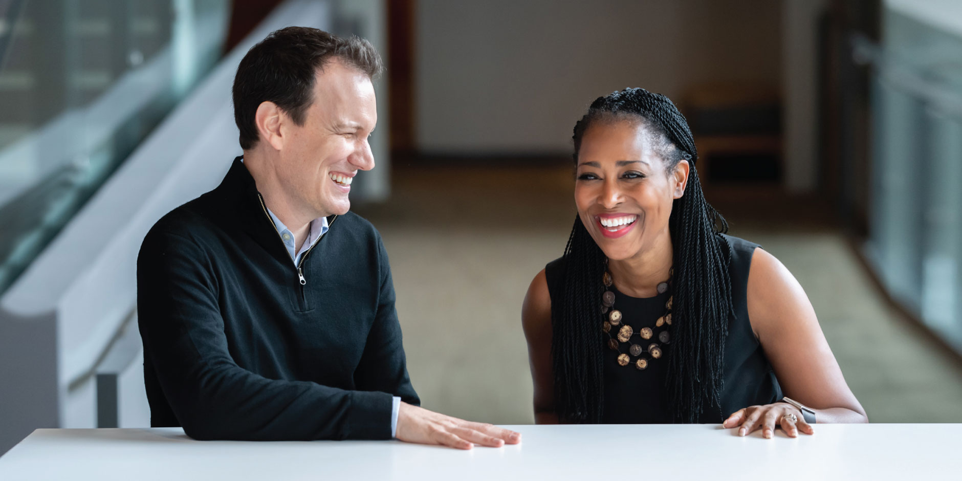 Shawn Achor (left) and Laysha Ward (right) laughing mid-conversation