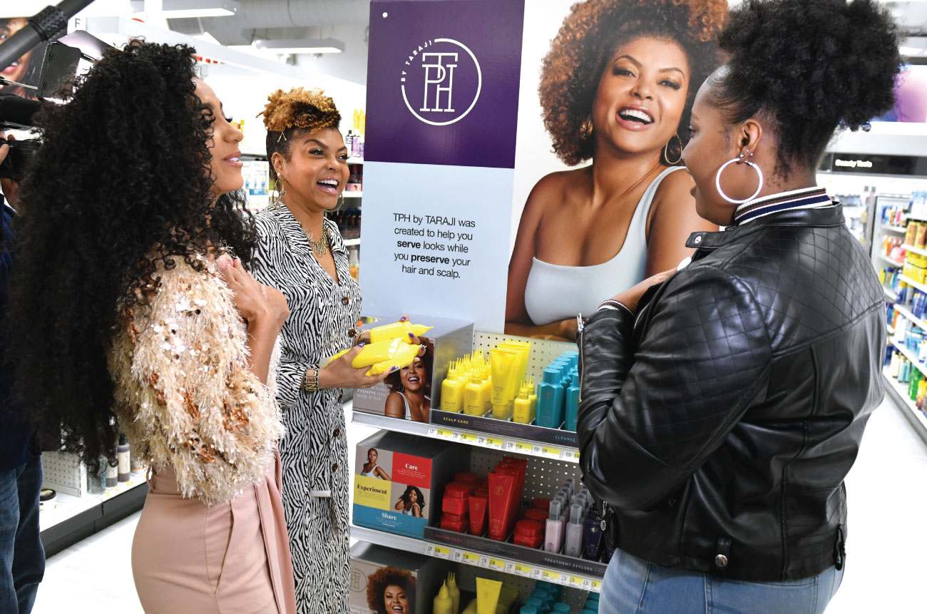 Taraji and two women discuss products at an endcap in a Target store