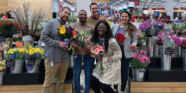 A group of Target team members smile in the floral area of a Target store