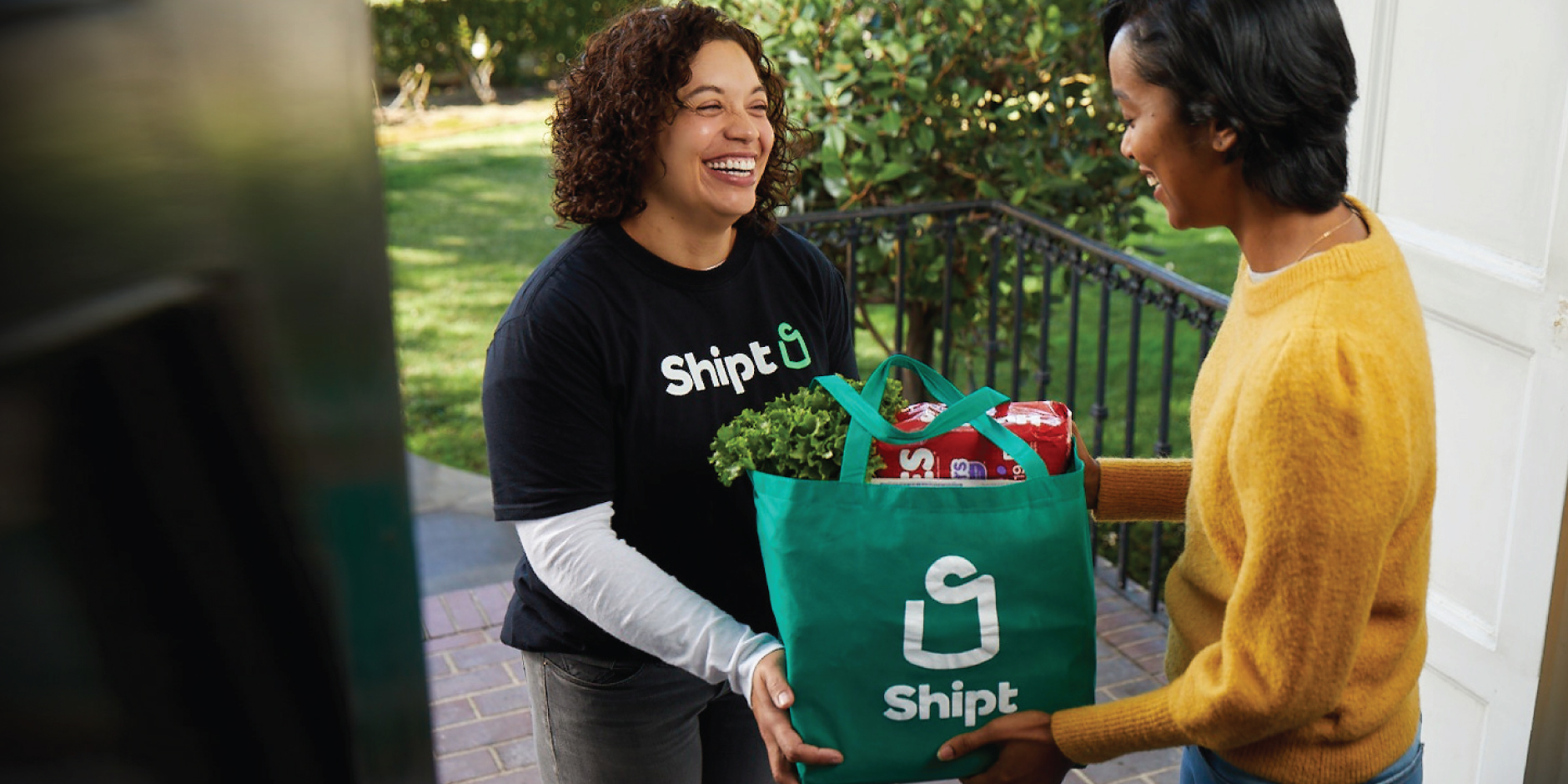 A Shipt Shopper in a black t-shirt smiles as she delivers a green bag to a guest on her doorstep