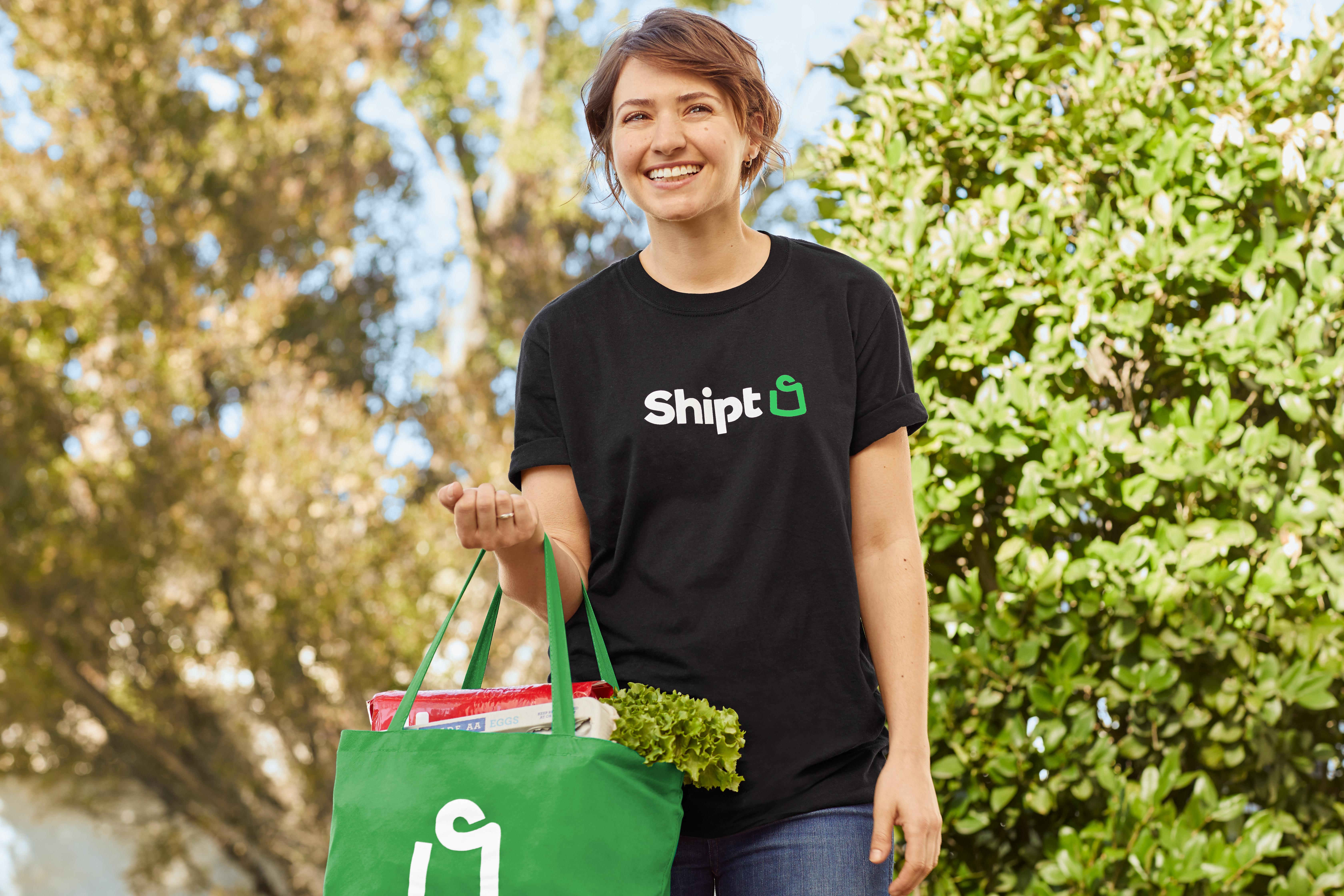 A Shipt Shopper in a black t-shirt smiles as the holds a green bag of groceries on her arm.
