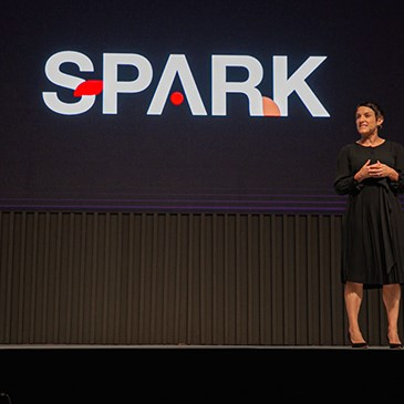 Tammy stands onstage wearing a black dress in front of a large screen that reads SPARK