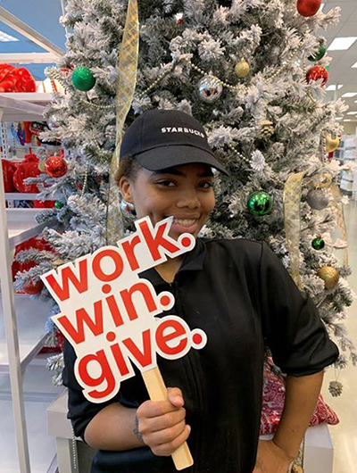 A woman in a black t-shirt and hat that reads Starbucks smiles and holds up a red work.win.give sign in front of a Christmas tree.