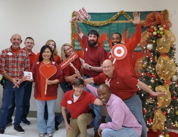 10 smiling team members in red shirts pose together near holiday decor as they hold up work.win.give signs