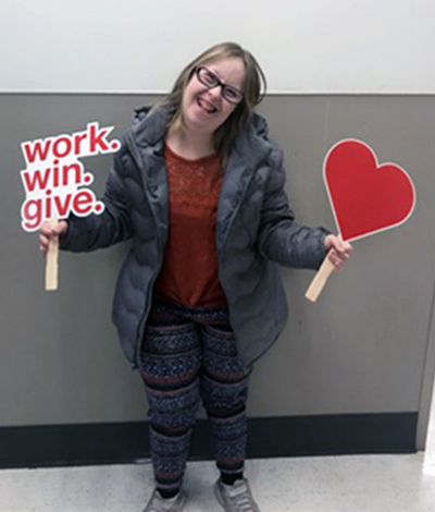A woman wearing glasses, a gray jacket, rust shirt and patterned leggings smiles as she holds up a work.win.give. sign and another heart-shaped sign.