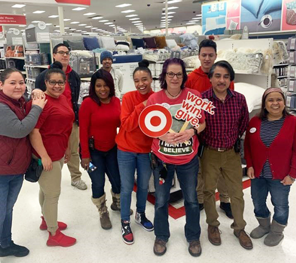 A group of 10 team members in red shirts stand in a Target bedding aisle laughing and holding assorted signs. Cymon stands in front; she has purple hair and glasses and is in a red shirt and blue jeans.