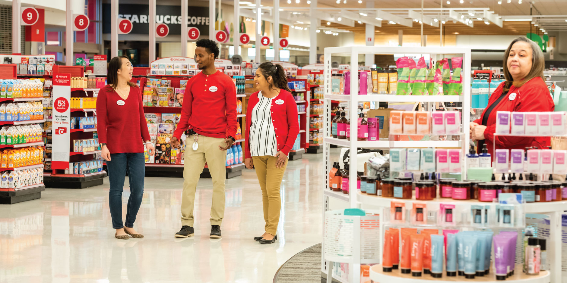 Three team members laugh as they walk an aisle. Nearby, a team member works on a product display.