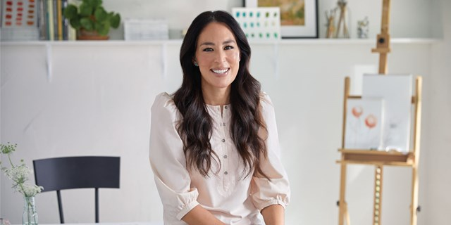 Joanna Gaines smiles in a pale pink top with sketches and art in the background