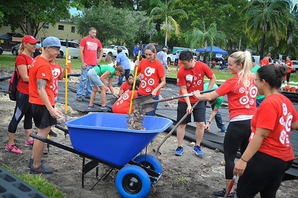 A group of volunteers in red shirts shovel mulch into a wheelbarrow as they build a new play space at a local school.