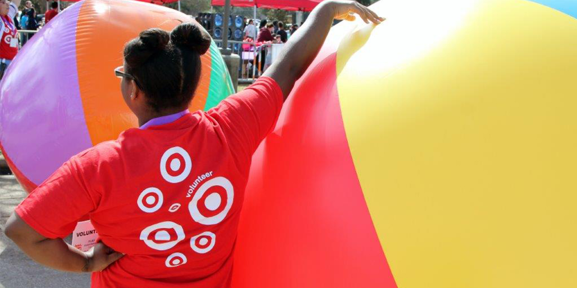 A team member in a red volunteer shirt leads an event with a giant beach ball