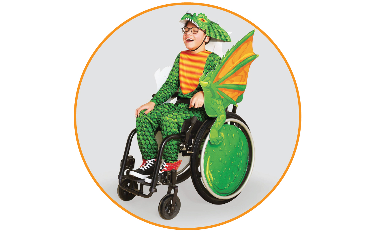 Jonas models a green and yellow dragon costume, with the wheels of his wheelchair decorated as wings.