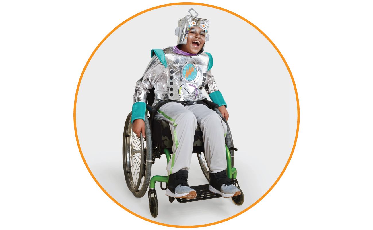 Elijah models a silver robot costume while smiling in his wheelchair