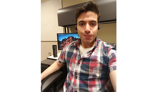 Asad sits at his home office with his computer. He has short brown hair and is wearing a plaid shirt and ear buds.
