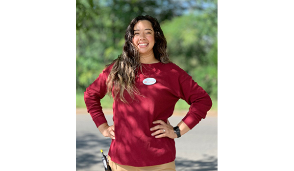 Melanie stands outside smiling with her hands on her hips. She's wearing red and khaki and a Target name badge and walkie-talkie, and has long, black hair.