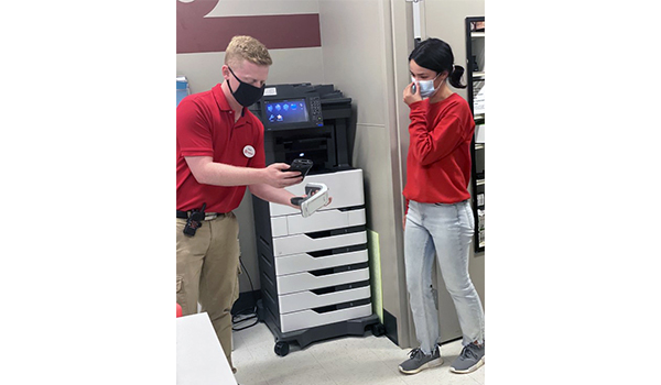 Shawn and a teammate stand in a Target backroom looking for a product together. They are both in red and khaki and wear face masks.