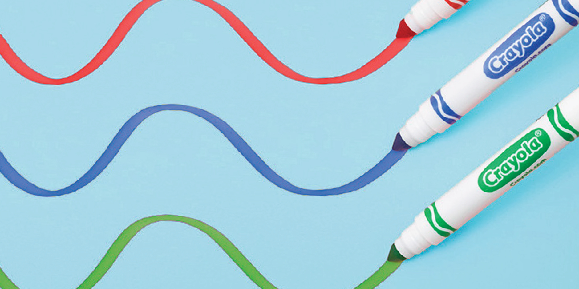 Three markers draw wavy lines on a blue background