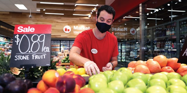 A team member wears a mask and gloves while grabbing fresh green apples in a Target store