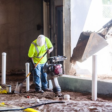 A construction worker uses a shovel on the exposed ground inside the Lake Street store.