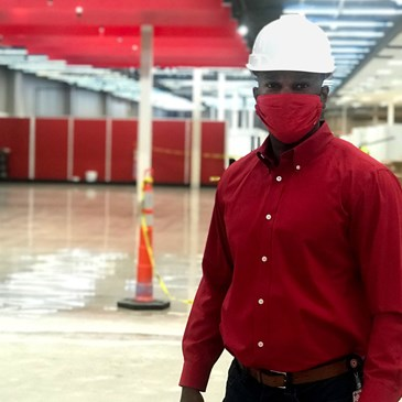 A man with a mask and hard hat stands inside the store, with construction underway behind him.