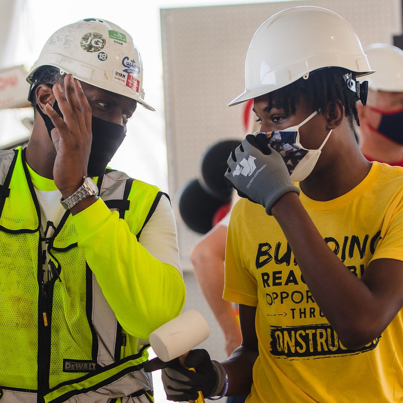 Two men in construction hard hats and masks discuss a project.