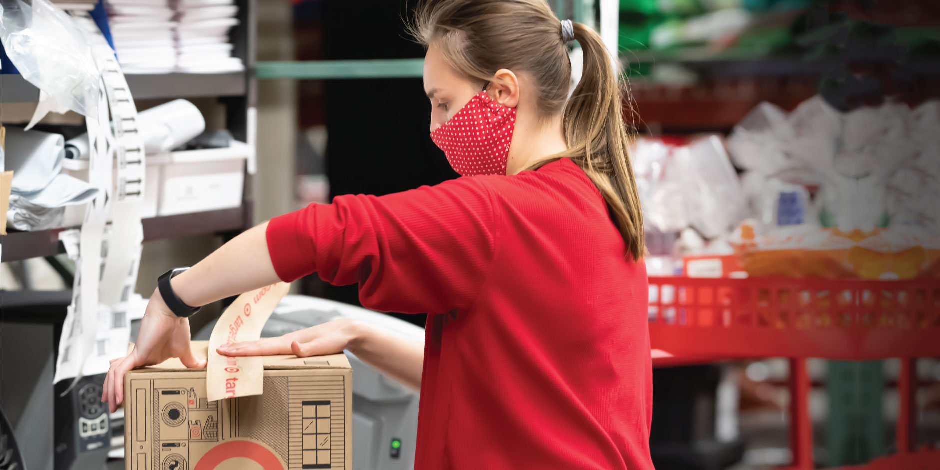 Woman in red polka dot face mask uses tape to secure a box.