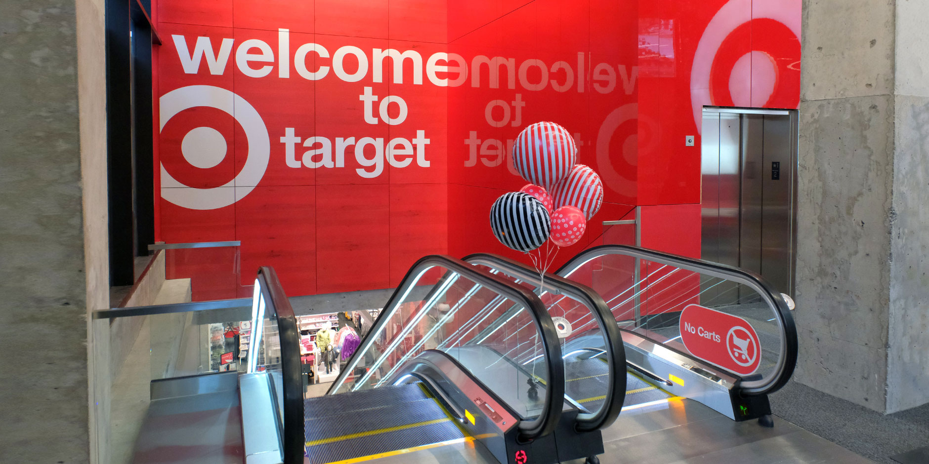 "A sign above a set of escalators reads ""welcome to Target"" on a red background."