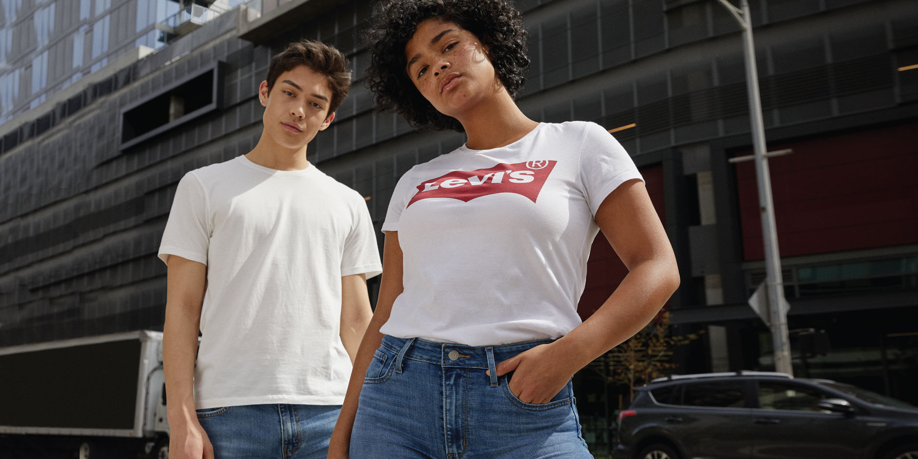 Two models pose in blue jeans and white tees. One tee features a red Levi's logo.