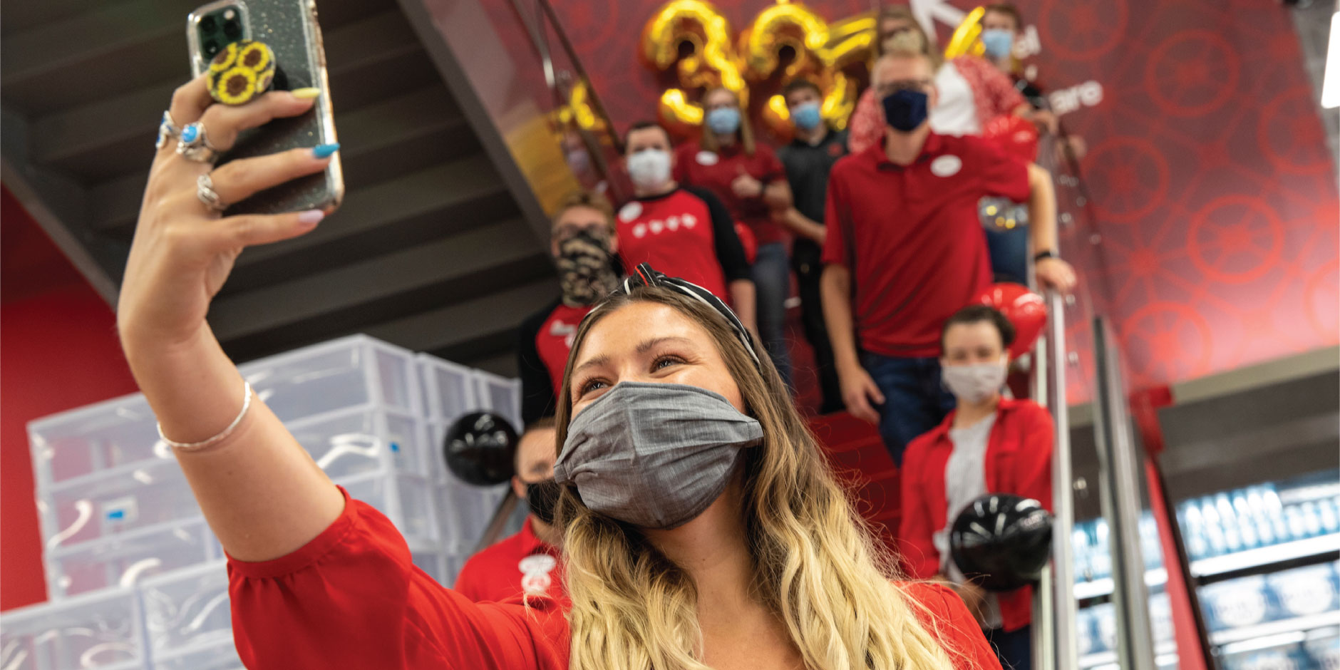 A team member wearing a red shirt and grey face mask takes a socially-distanced selfie with a group of team members on an escalator behind her