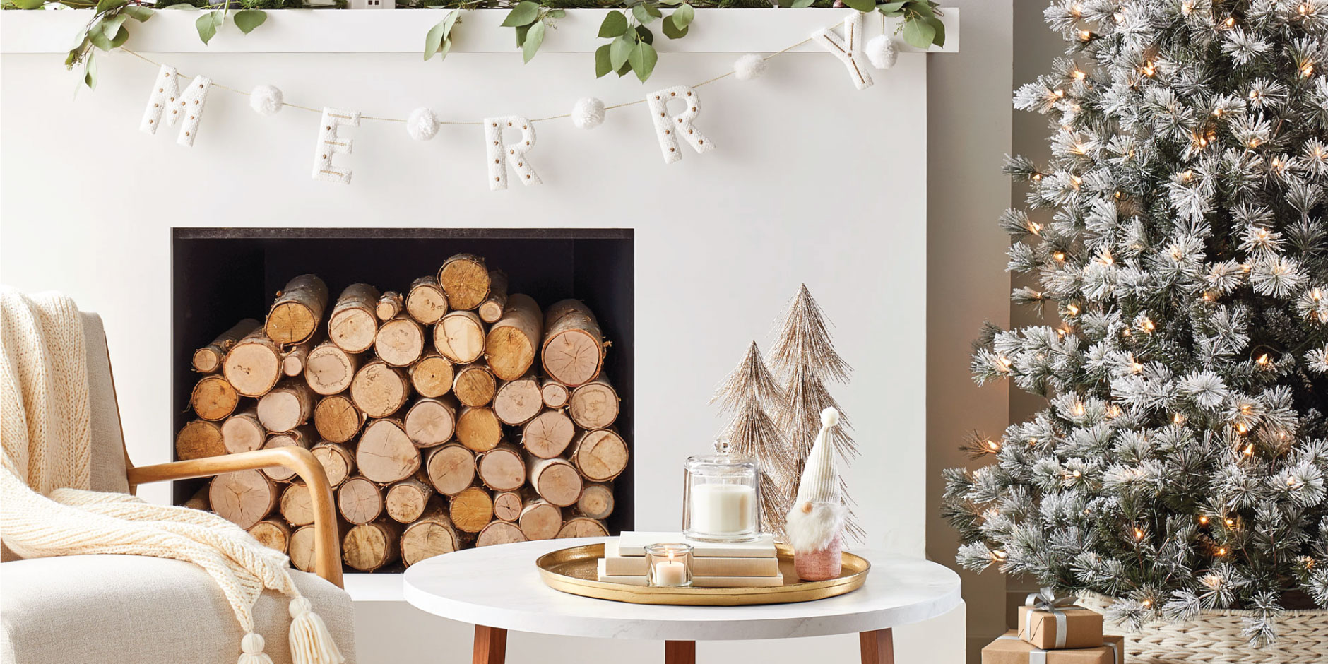 A cozy living room scene including neutral-colored decor and a merry garland across a mantle