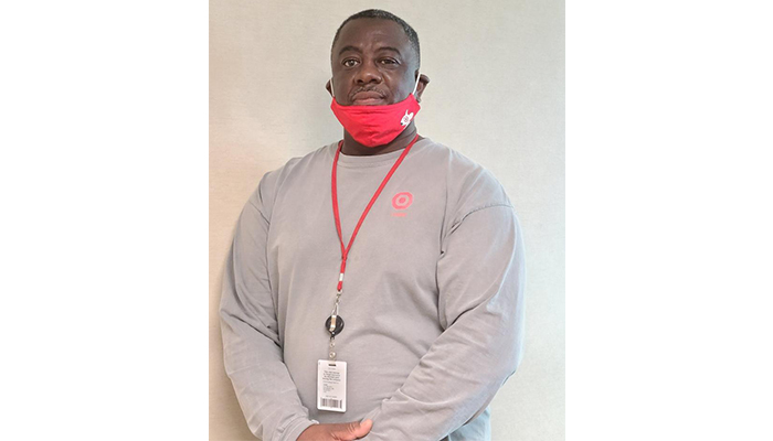 A head-and-shoulders shot of Calvin, wearing a gray shirt, red face mask and Target lanyard