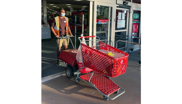 Jodi, wearing a mask and safety vest, pushes a Target cart through the entrance door.