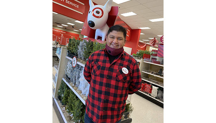 Jose stands at the entrance near a statue of Bullseye the dog. He's wearing a red plaid shirt and mask.