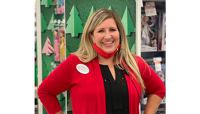 Kristin stands in front of a holiday display smiling and wearing a red shirt and mask pulled down at her chin.